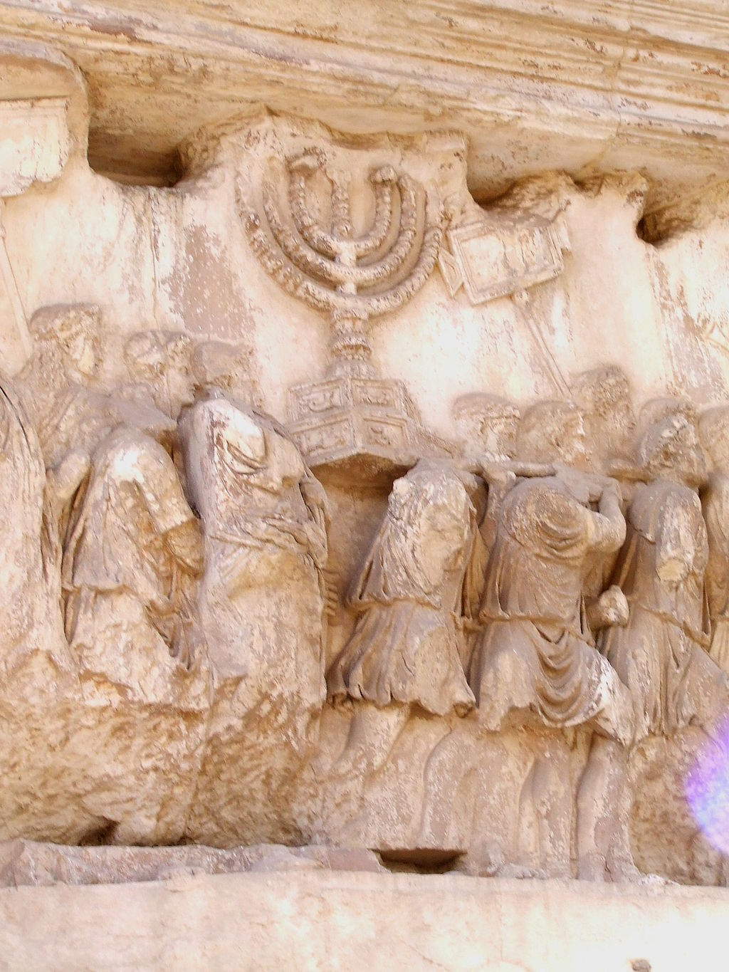 1024px Carrying_off_the_Menorah_from_the_Temple_in_Jerusalem_depicted_on_a_frieze_on_the_Arch_of_Titus_in_the_Forum_Romanum